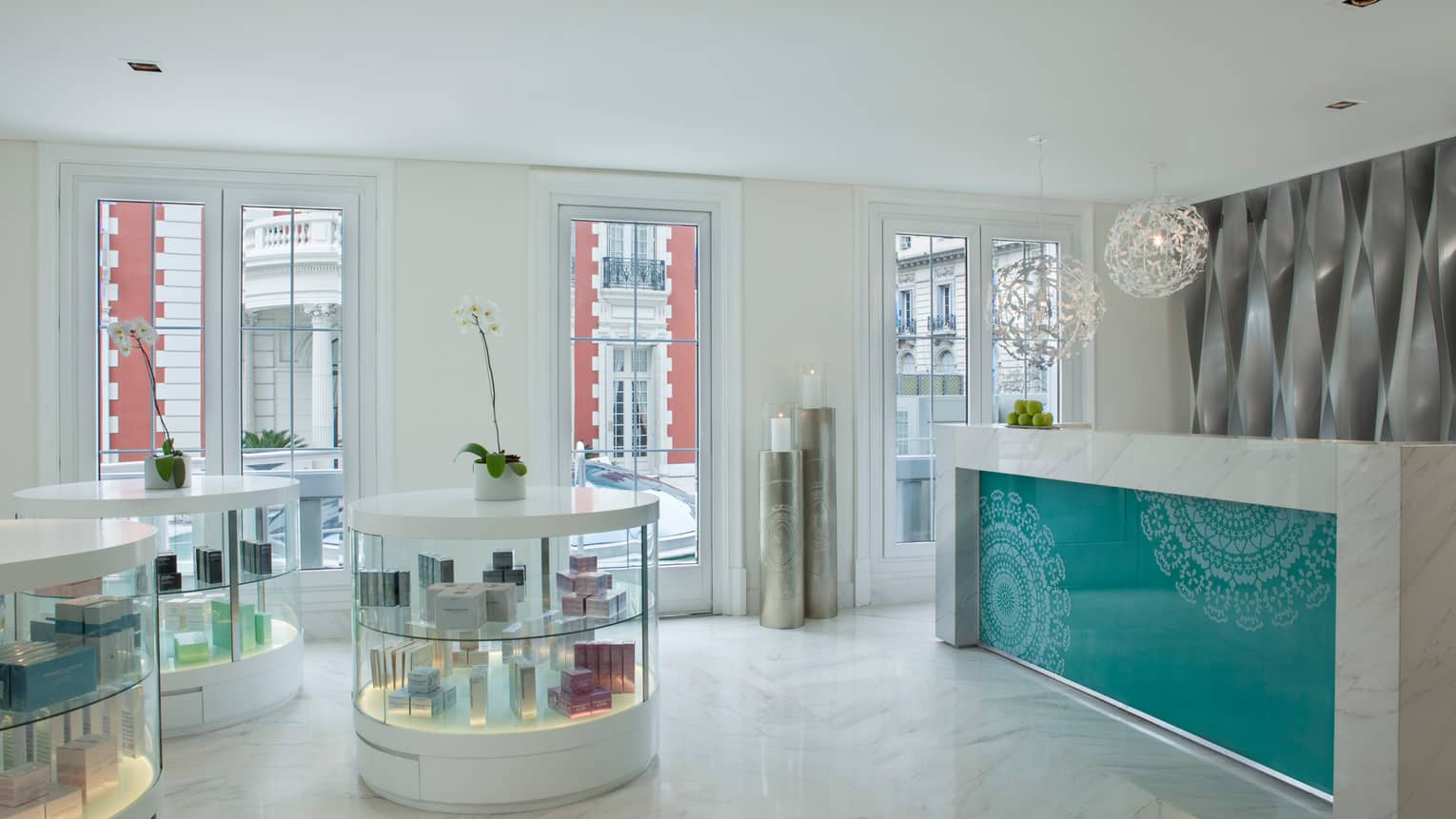 White marble spa lobby with round glass display cabinets, desk with teal pattern, white lamp