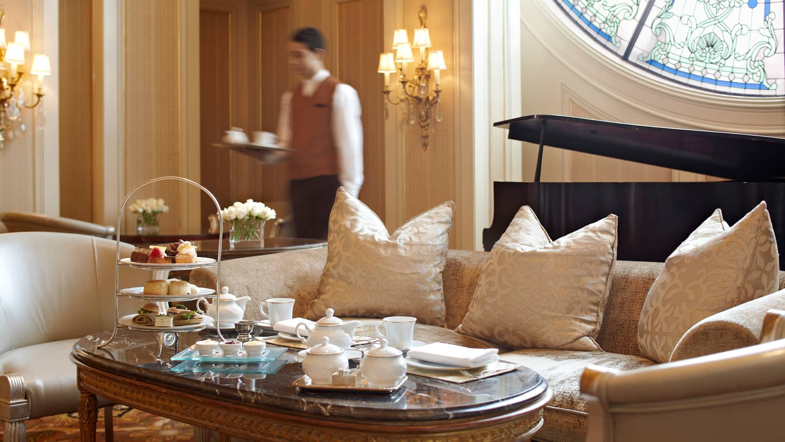 Formal tea service, sandwiches and dessert on table in front of white satin sofa