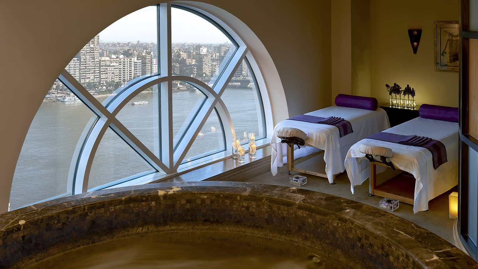 Two massage tables side-by-side in couples spa suite by lare crescent-shaped window overlooking Nile