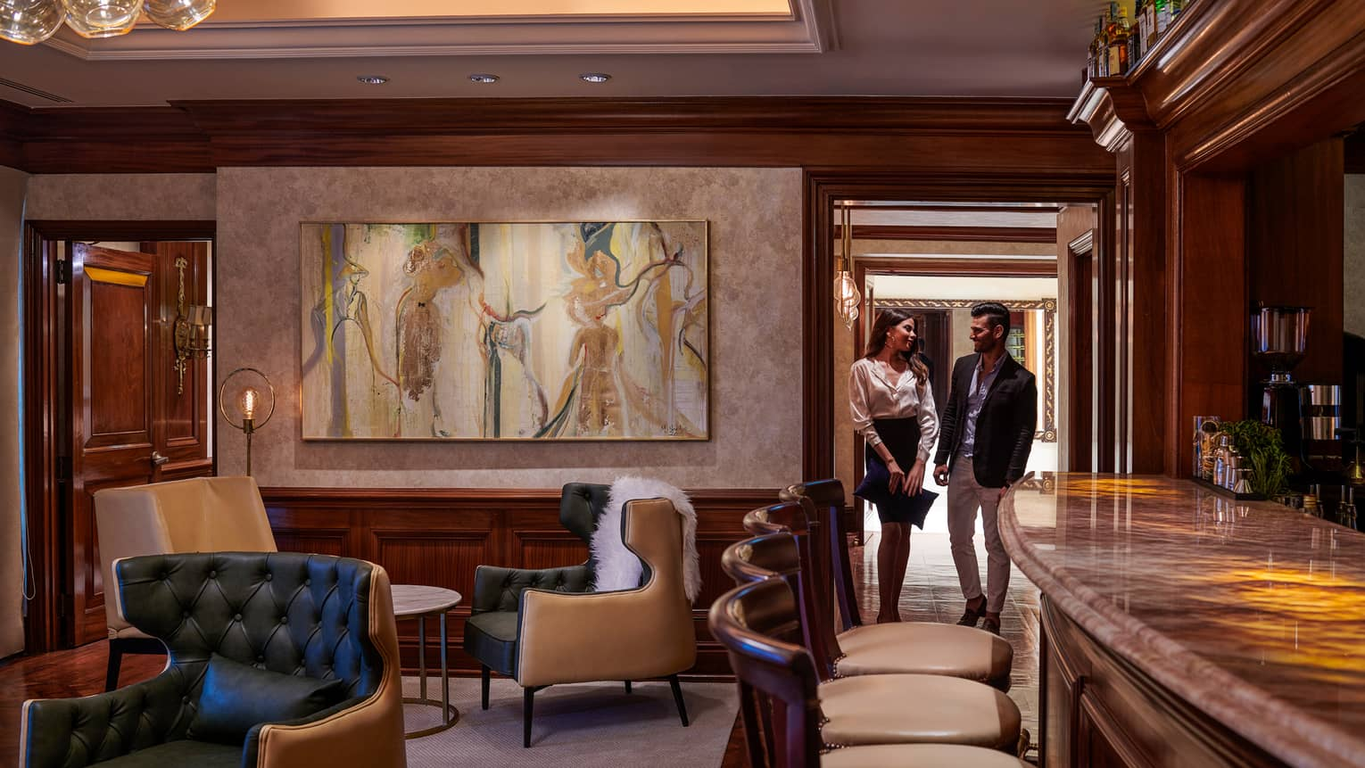 Woman and man walk through door into cocktail lounge with large painting, leather chairs
