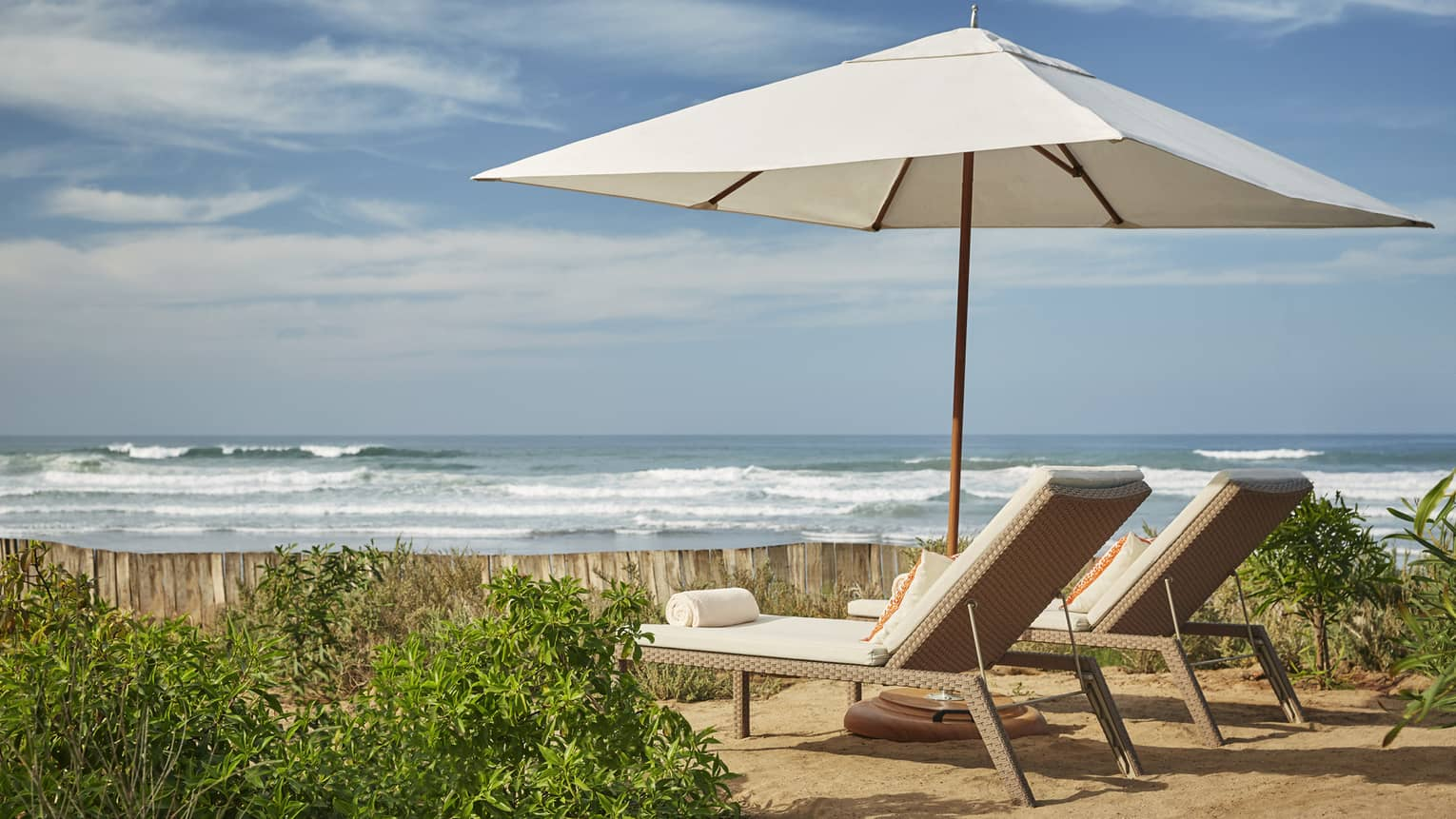 Lounge chairs under white beach umbrella on golden sand, Atlantic Ocean