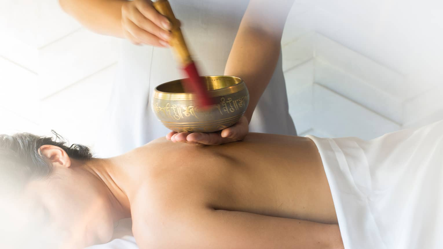 Hands play brass singing bowl over bare back of woman lying on massage table