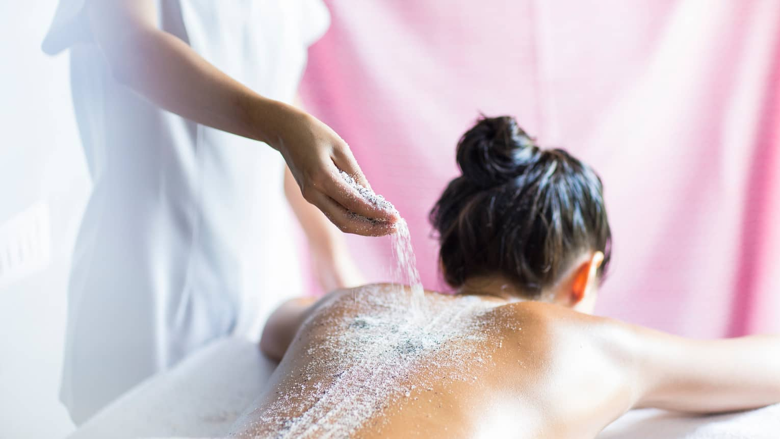 Spa staff pours salts, sand over woman's bare back as she lies on treatment room table