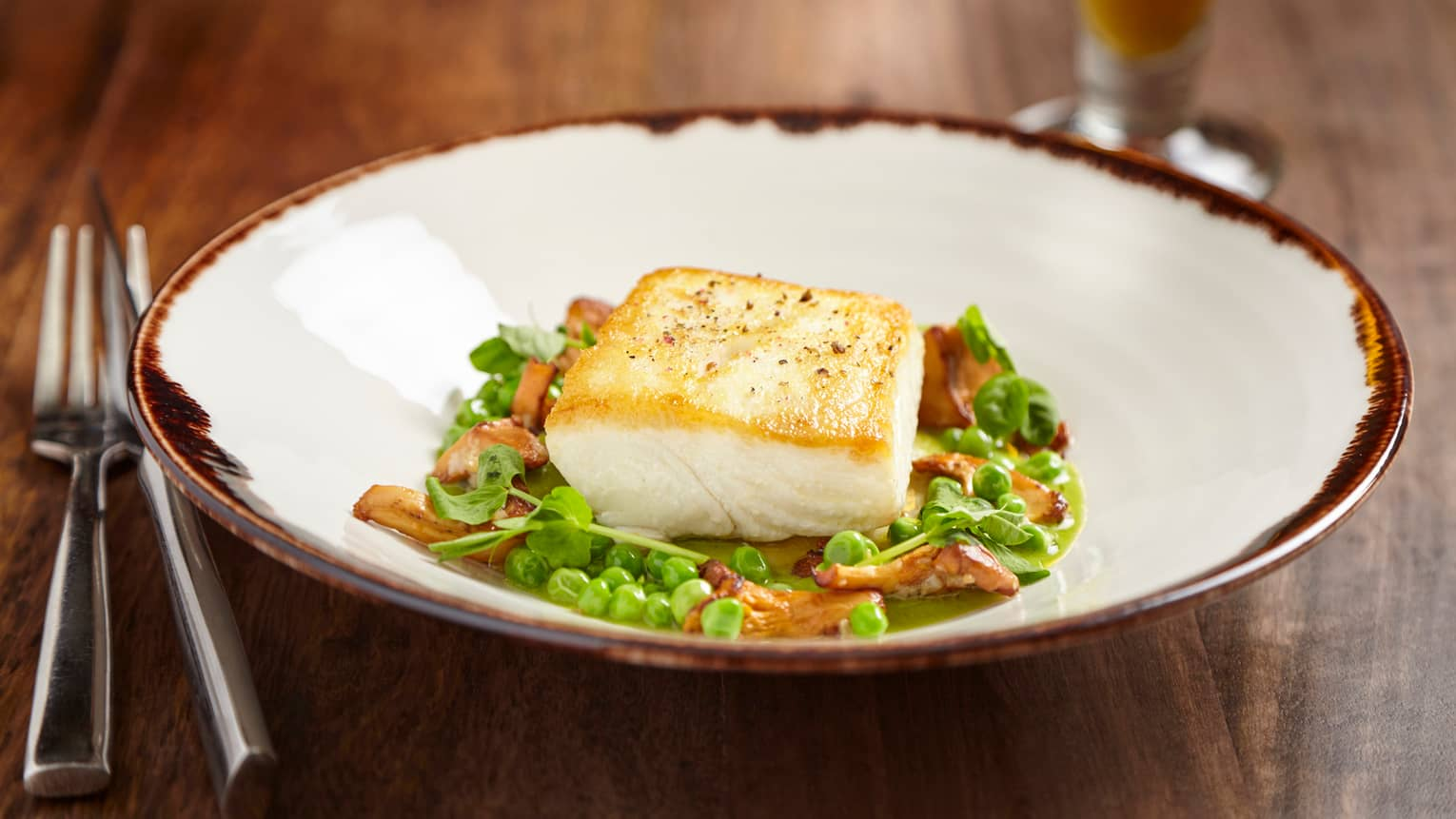 Pan-roasted Alaskan halibut fillet on fresh green peas, herbs and mushrooms in bowl
