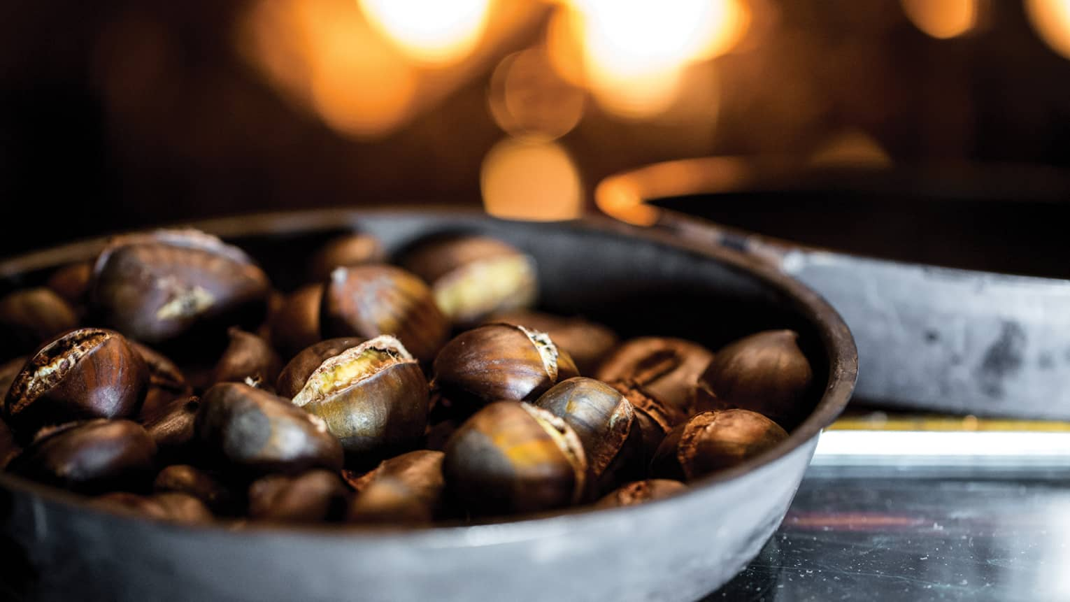 Zuppa di Castagne, chestnuts in stainless-steel pan in front of a fire