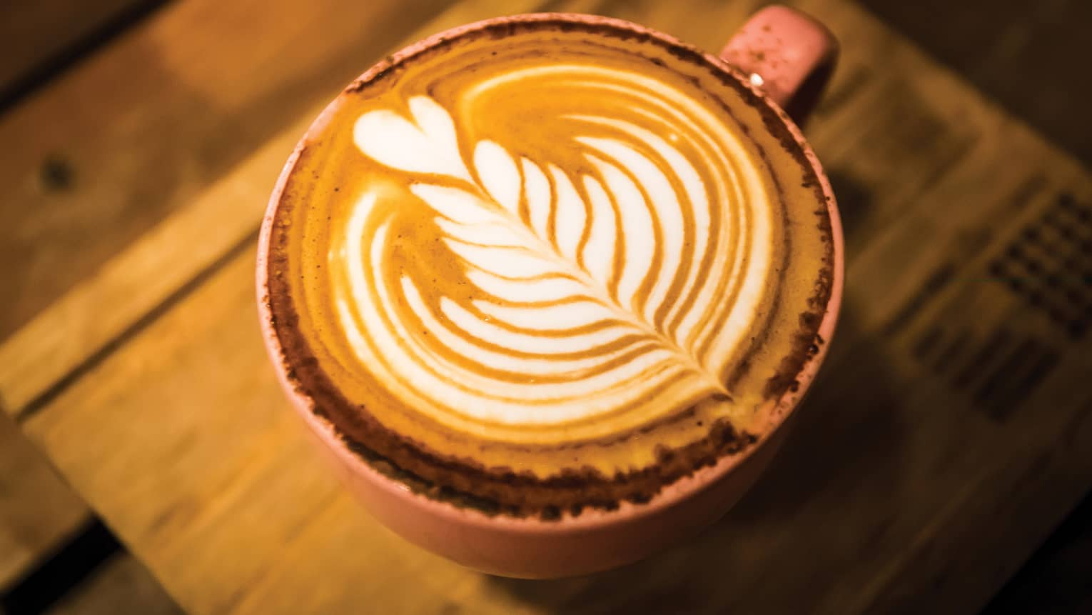 Close-up of latte coffee with flower design in foam