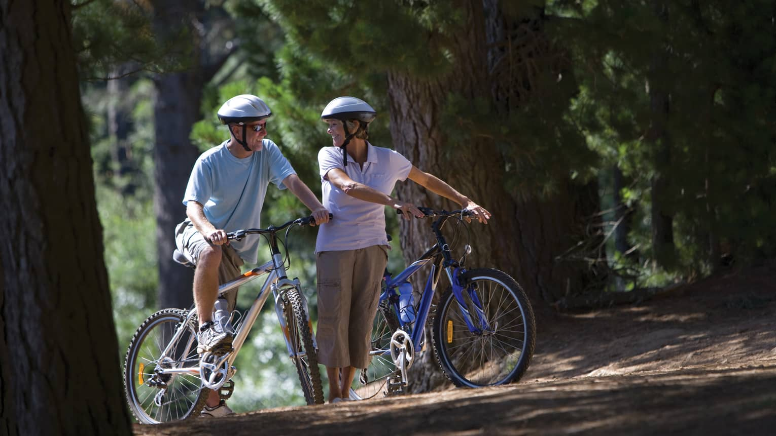 Smiling man and woman wearing helmets, sunglasses pause with their bicycles on forest path