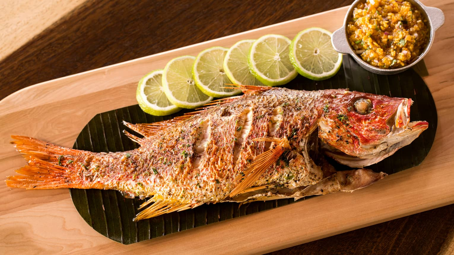 Whole grilled fish with marinated, flaking skin on black platter with row of lemon slices, chayote slaw in bowl