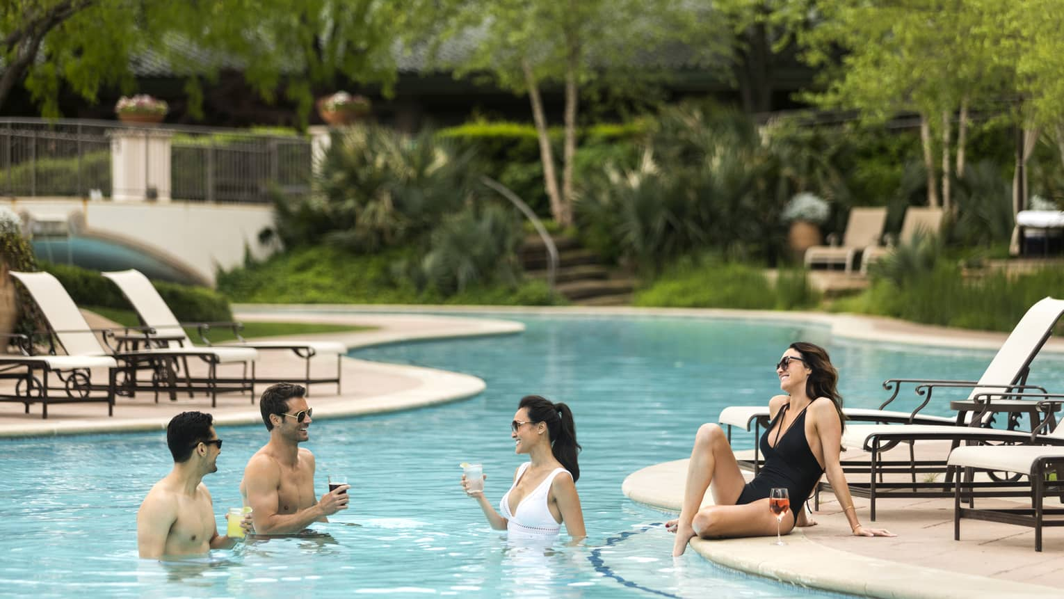Two men and two women relaxing in and near a pool, trees and greenery in the background.