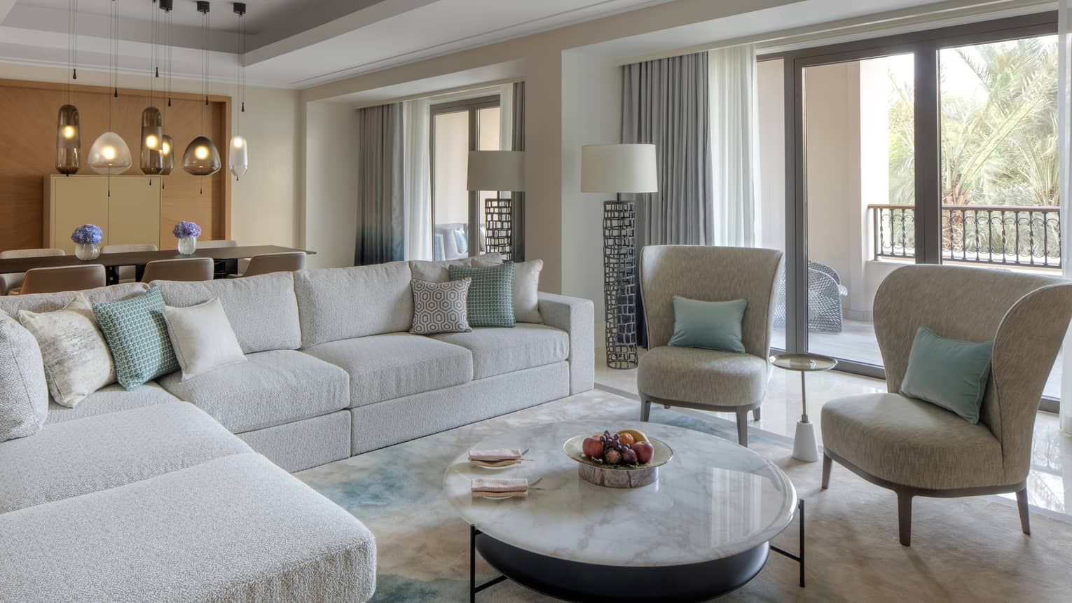 Living room with light beige sectional sofa, two cushioned chairs, round coffee table, balcony