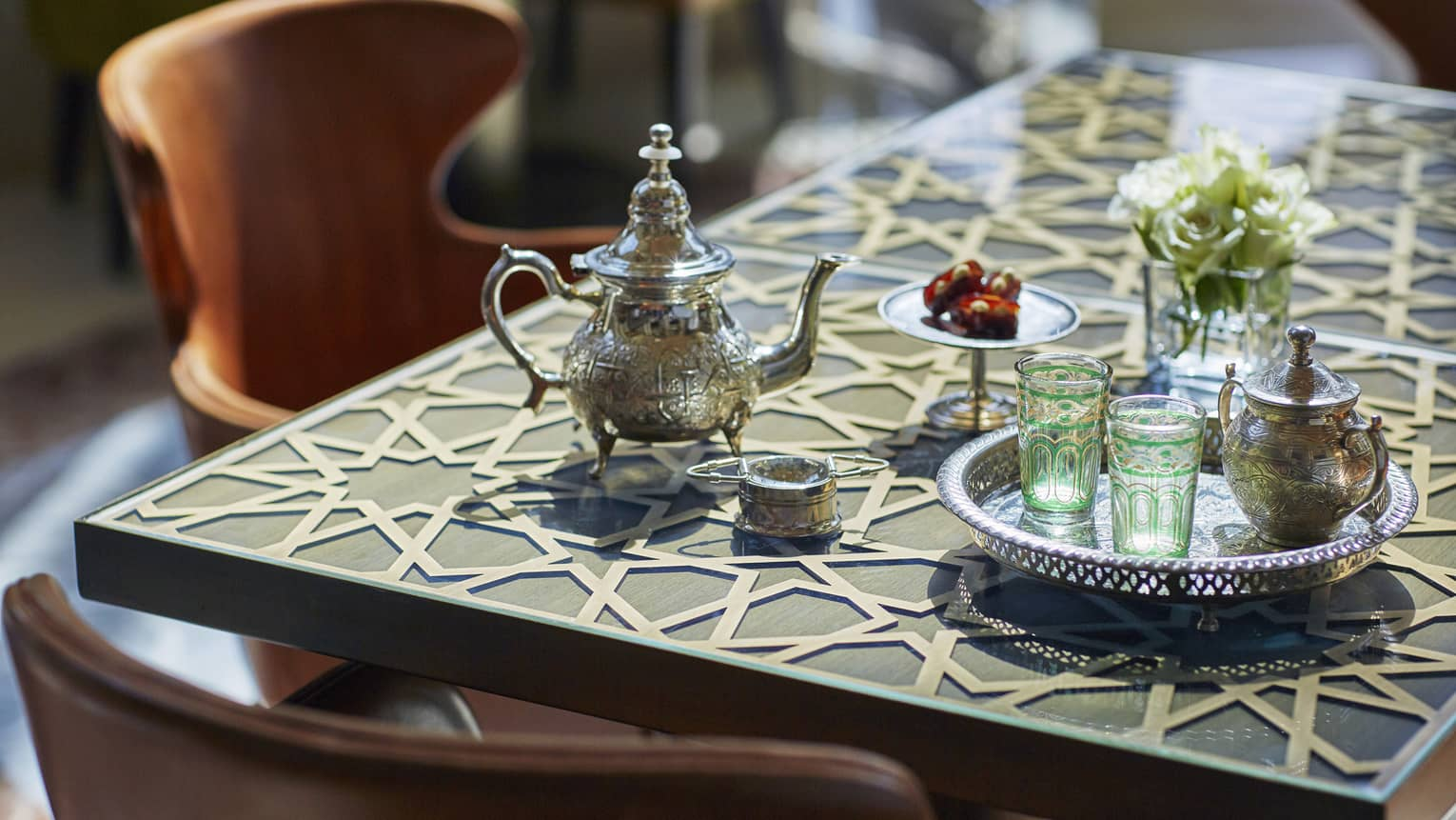 Small Moroccan-style tea pot and colourful glasses on silver tray on table