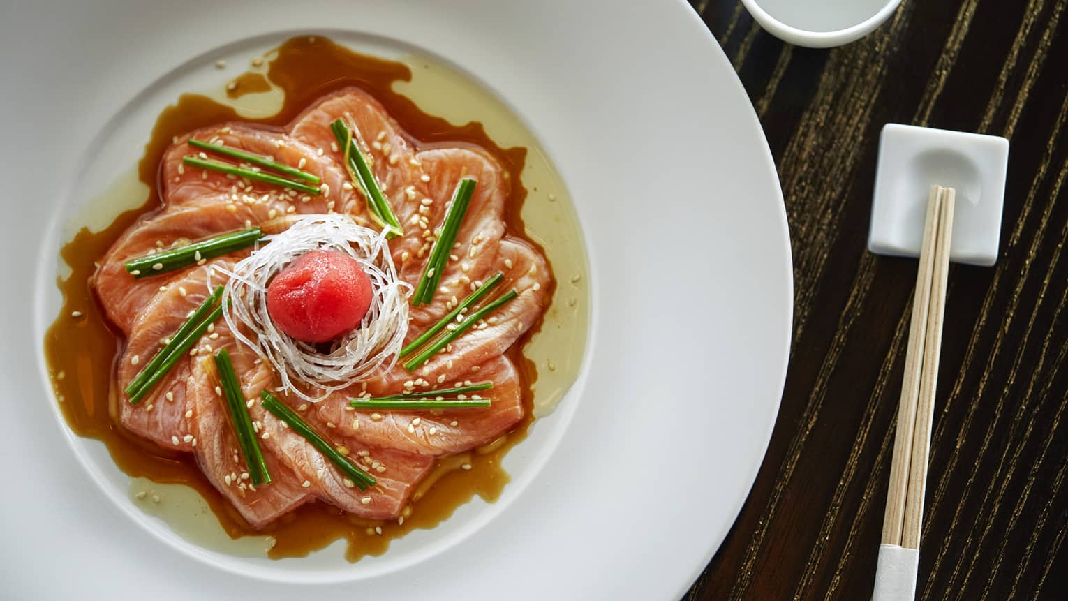 Aerial view of sashimi arranged as flower in dish, sauce and garnish
