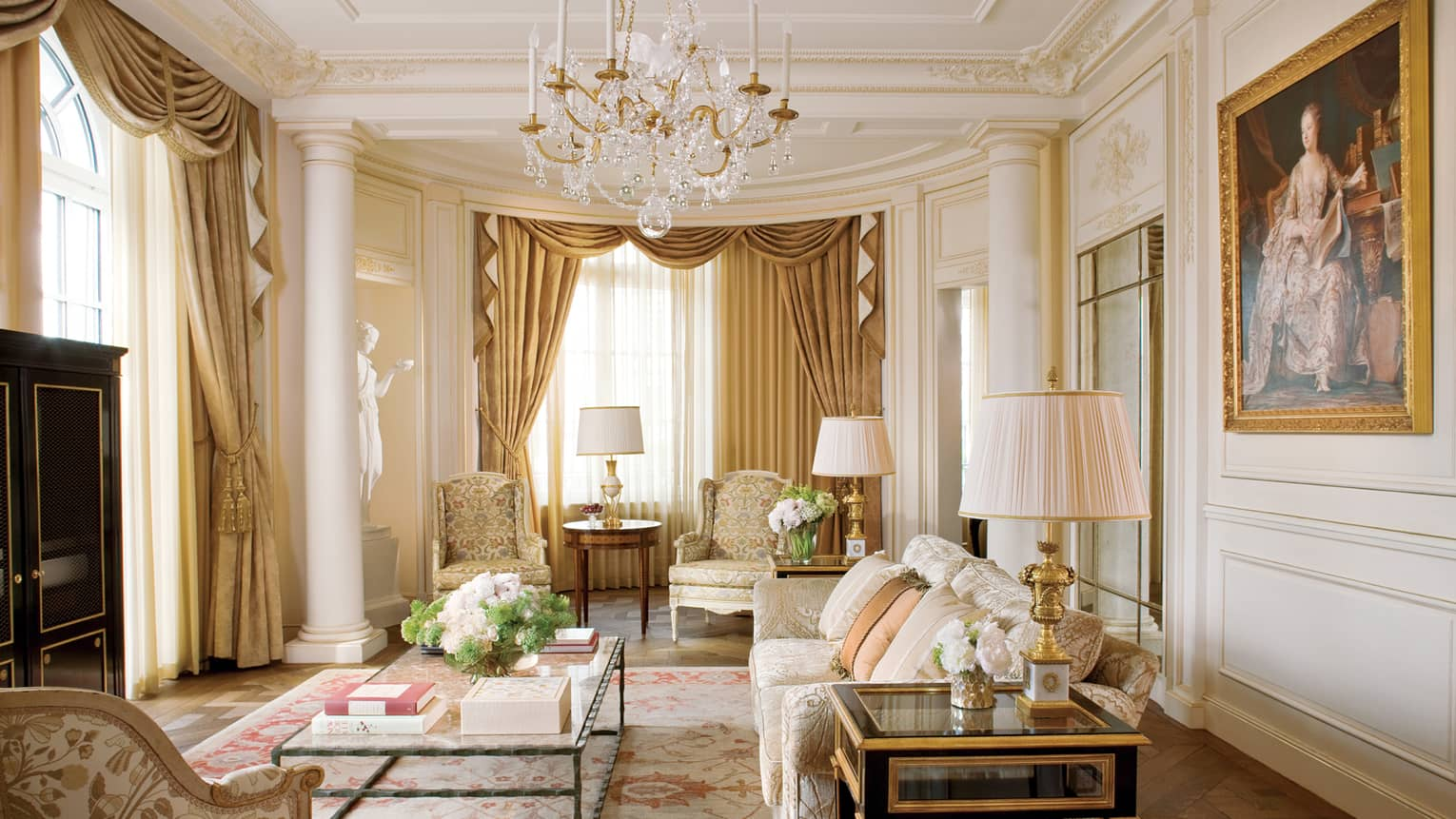 Elegant Royal Suite living room with cream floral sofas and decor, crystal chandelier, white statue, large oil painting