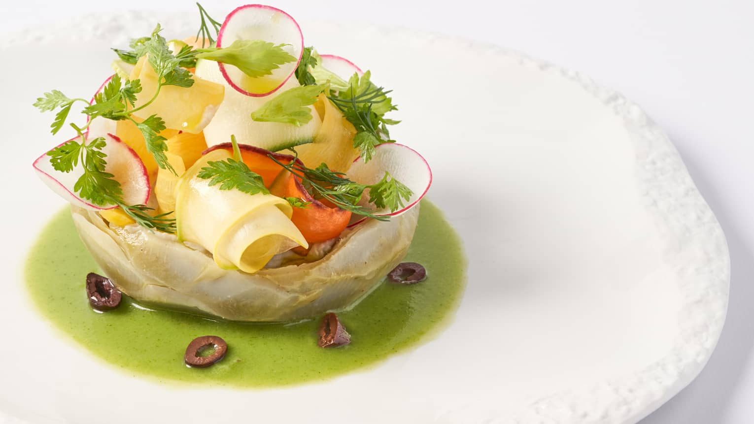 Camus artichokes in vinaigrette of young yegetables on white round plate