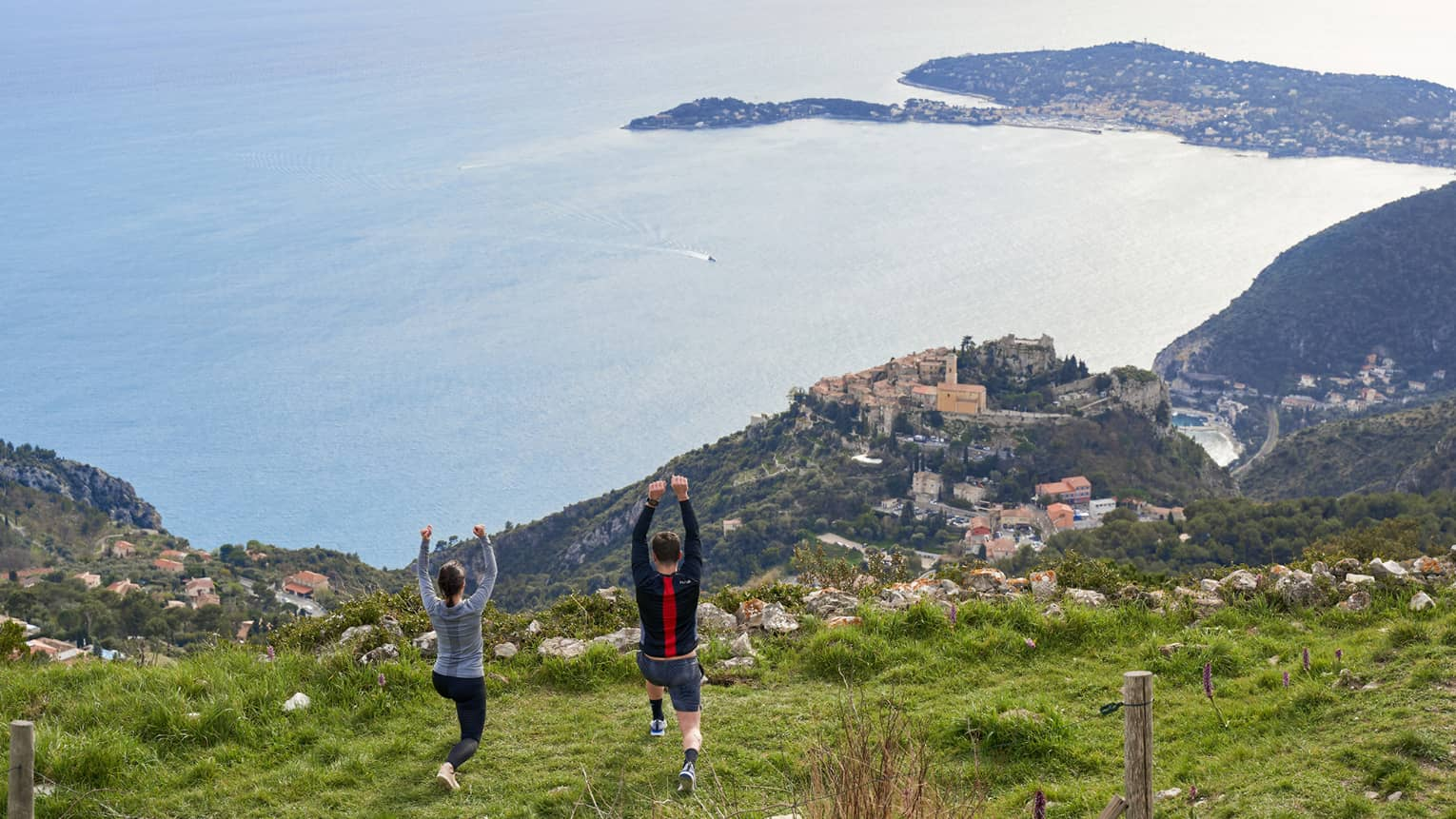 Rear view of woman and man doing yoga on green hilltop overlooking Mediterranean Sea