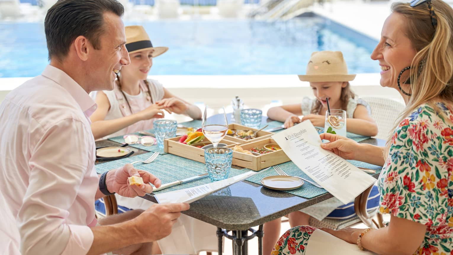 Couple seated with two girls wearing straw hats, talking over Club Dauphin menus poolside