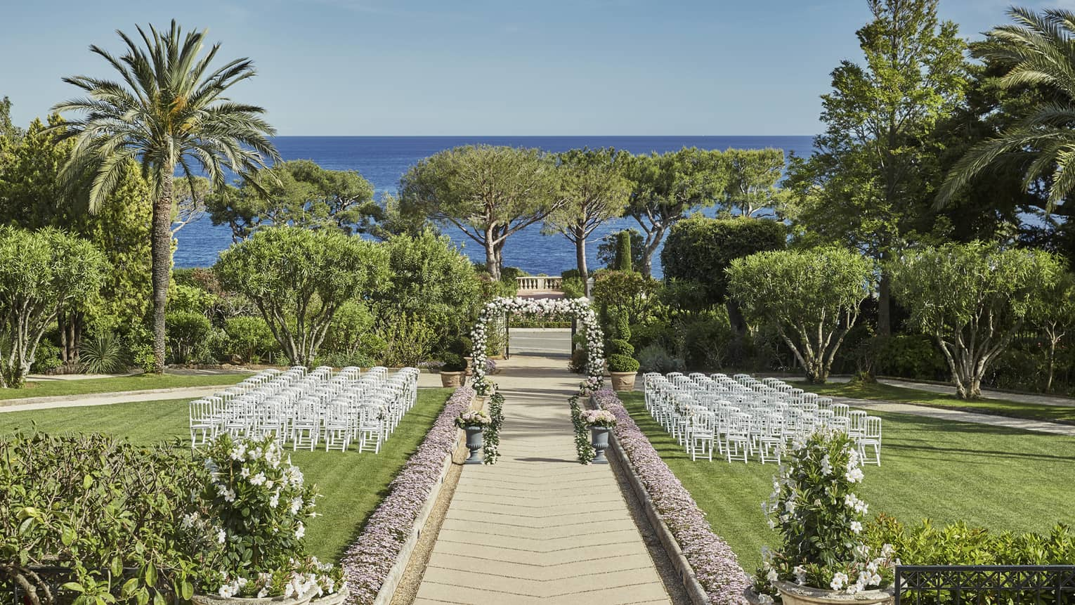 View down garden path to wedding altar with rows of white chairs on either side