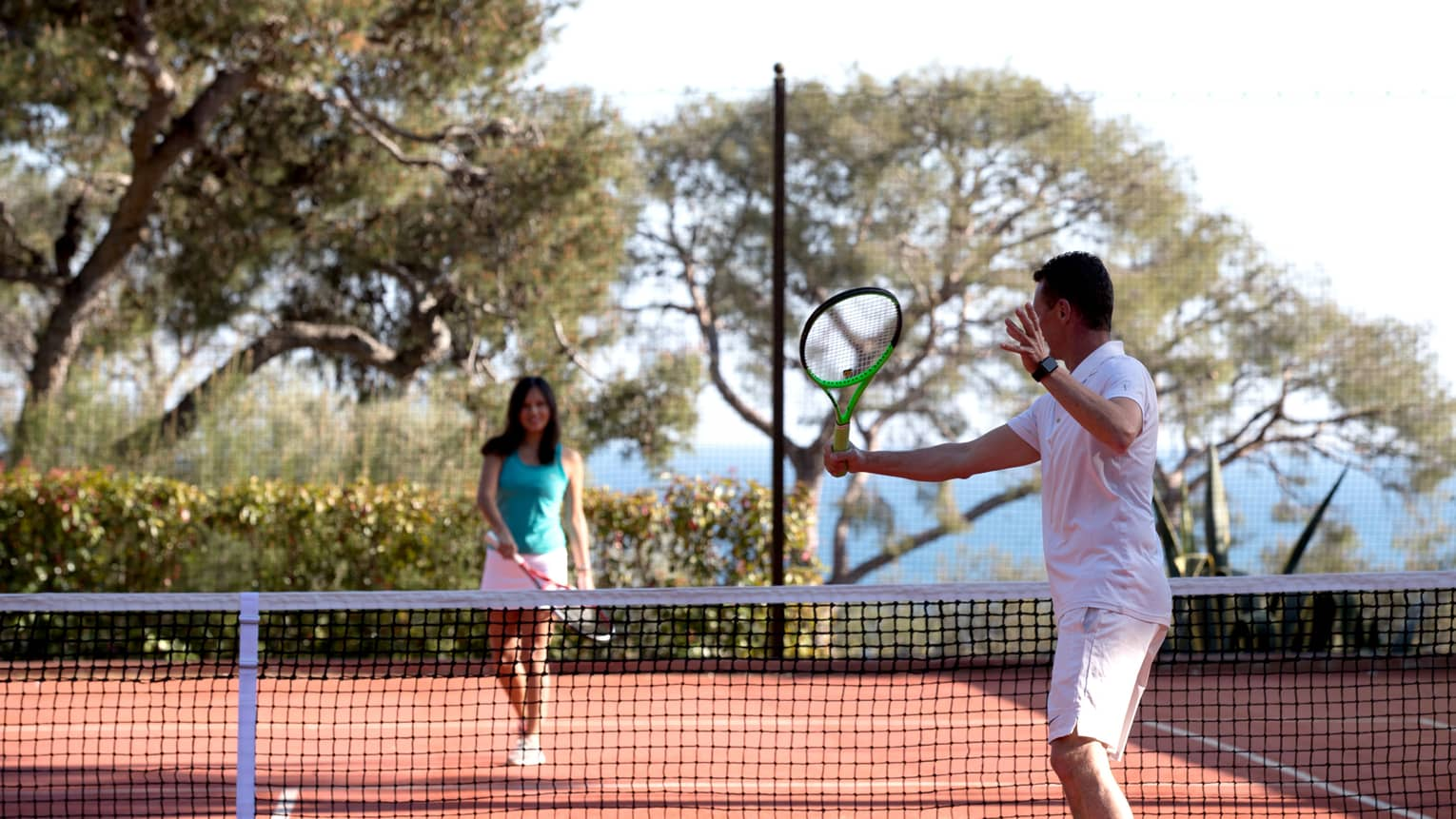 Man swing tennis racket, woman on other side of net