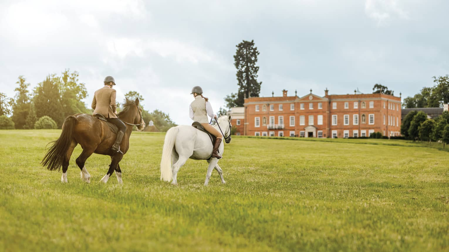 Couple rides horses across green English field to Four Seasons Hotel Hampshire building