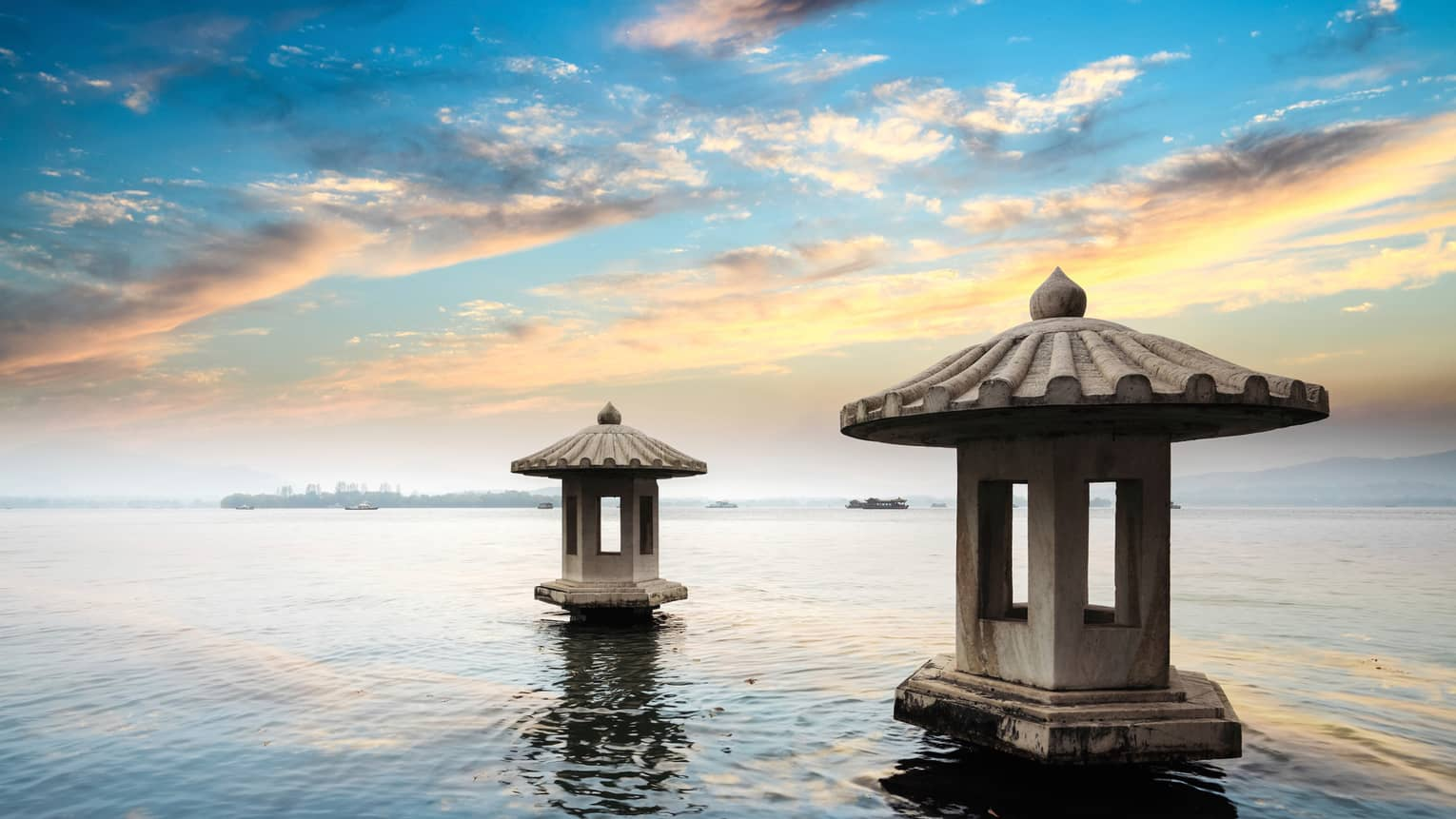 Sunset reflected on West Lake, two cement pagoda structures in water