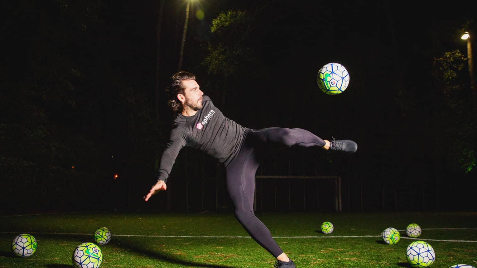 POWA by sphere session, Michael Chabala kicks soccer ball in mid-air on field with multiple balls at night