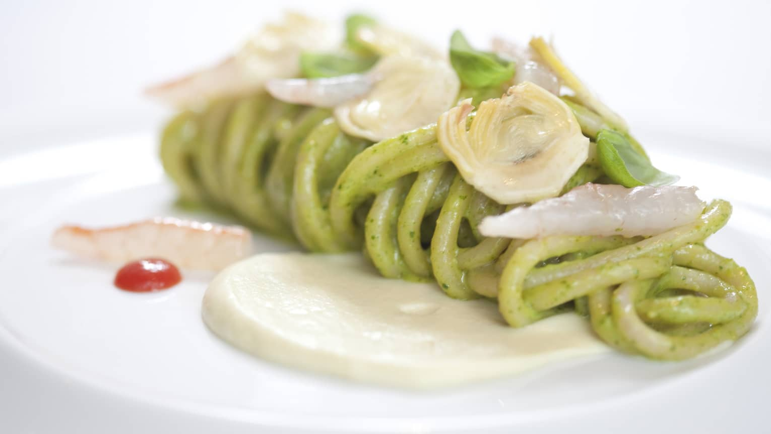 Pesto pasta with prawn tails and artichoke hearts, garnished with white sauce and basil leaves