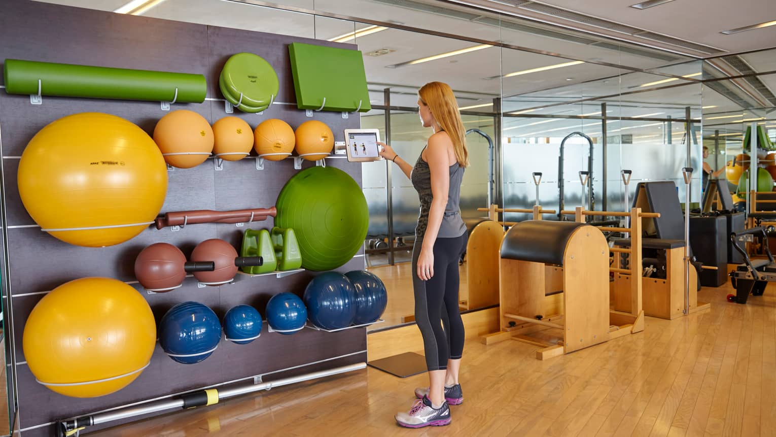 Fitness Centre, woman in workout gear taps taps touch screen by wall with colourful pilates balls, weights