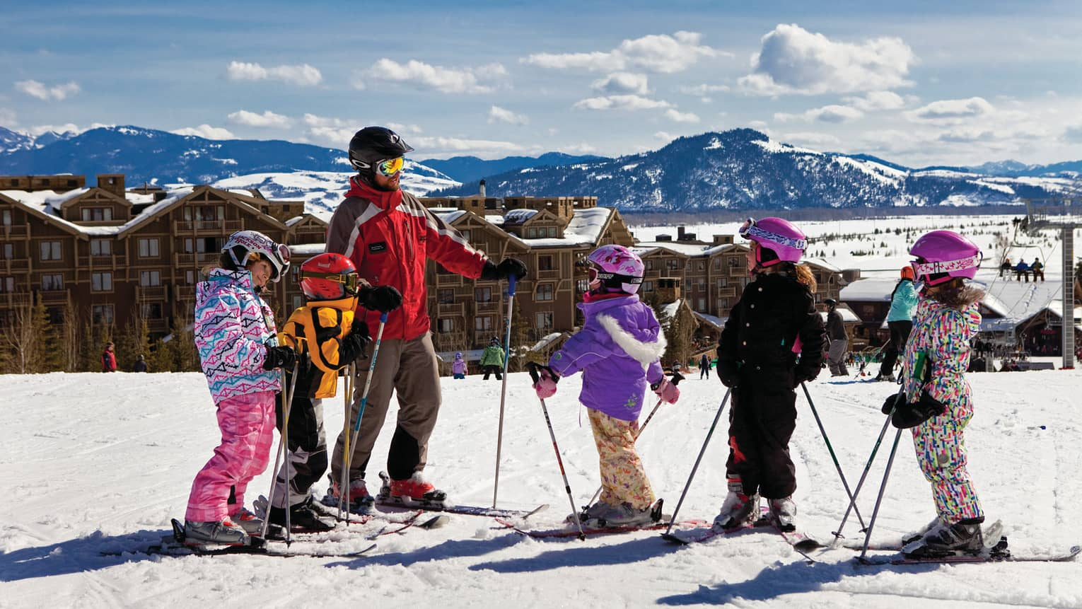 Children wearing skis, winter gear on sunny hill with instructor, hotel in background