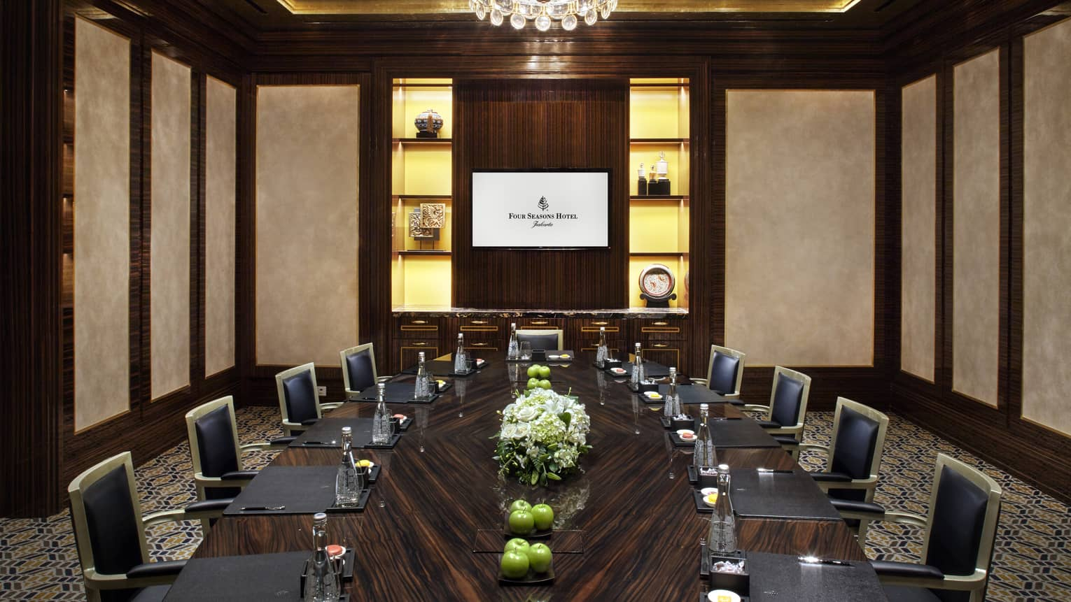 Meeting room with large wood boardroom table lined with executive chairs