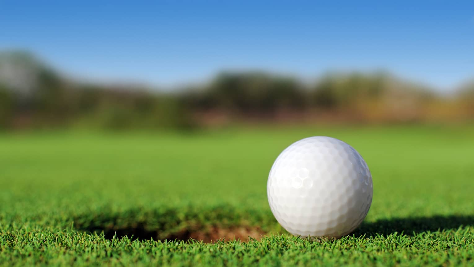 A close up of a white golf ball sitting right next to a golf hole on the course