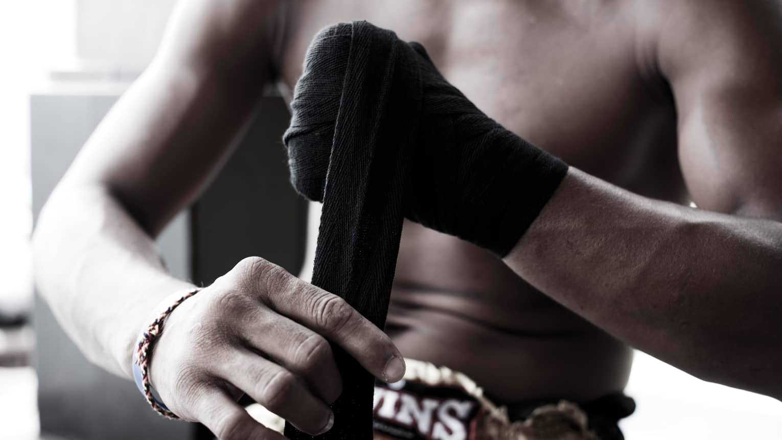 Close-up of Muay Thai boxer wrapping black boxing tape around hands