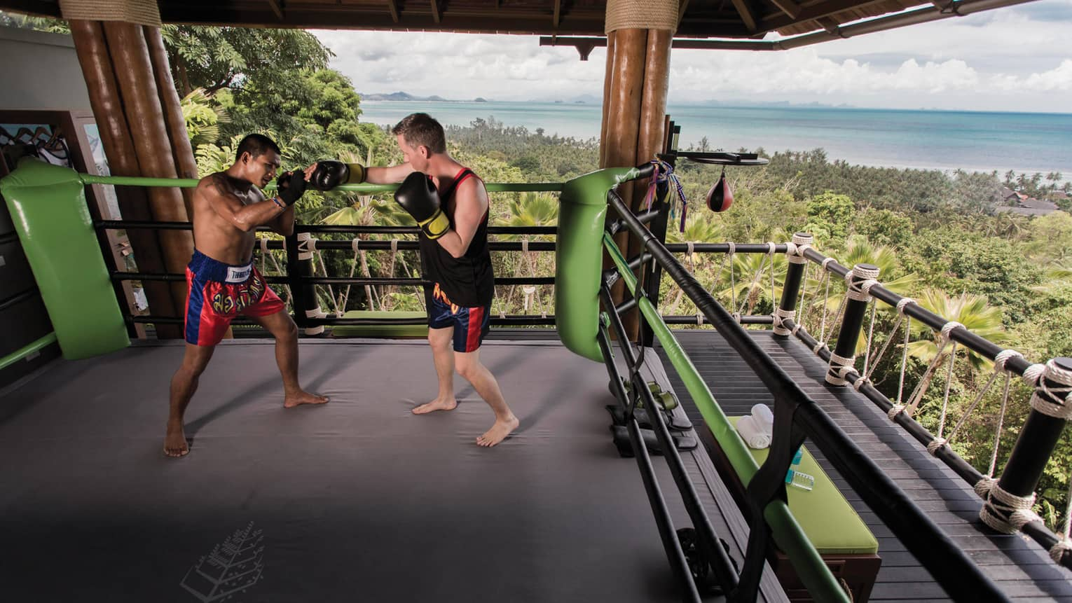 Two boxers practice in Muay Thai boxing ring high up in mountain