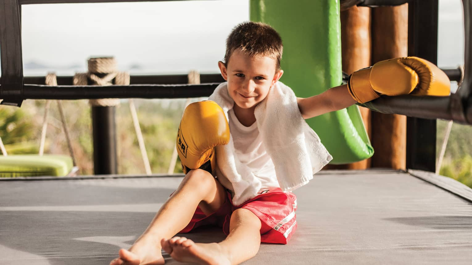 Smiling young boy with white towel around neck, boxing gloves sits in sunny outdoor ring