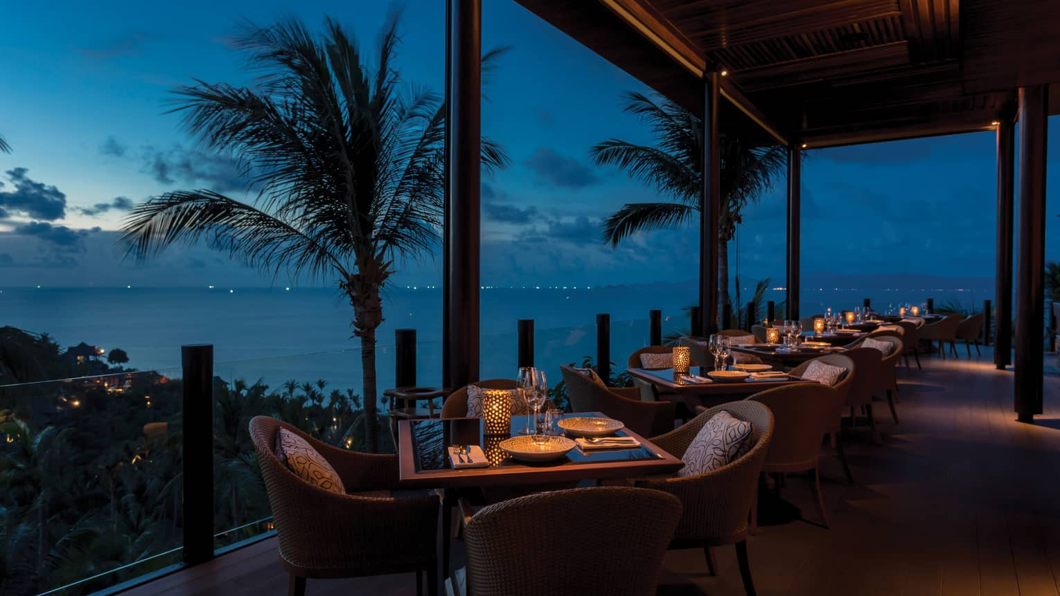 Outdoor terrace at Koh Thai Kitchen in Koh Samui, view of palm trees and Gulf of Thailand