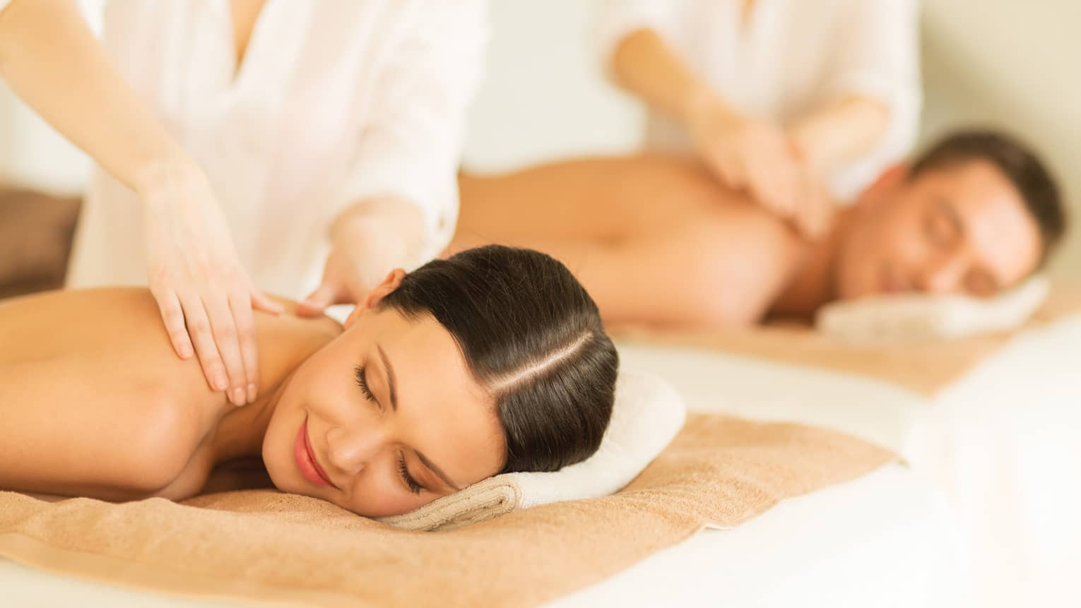 Woman and man lie side-by-side on massage tables as spa staff massage their bare shoulders