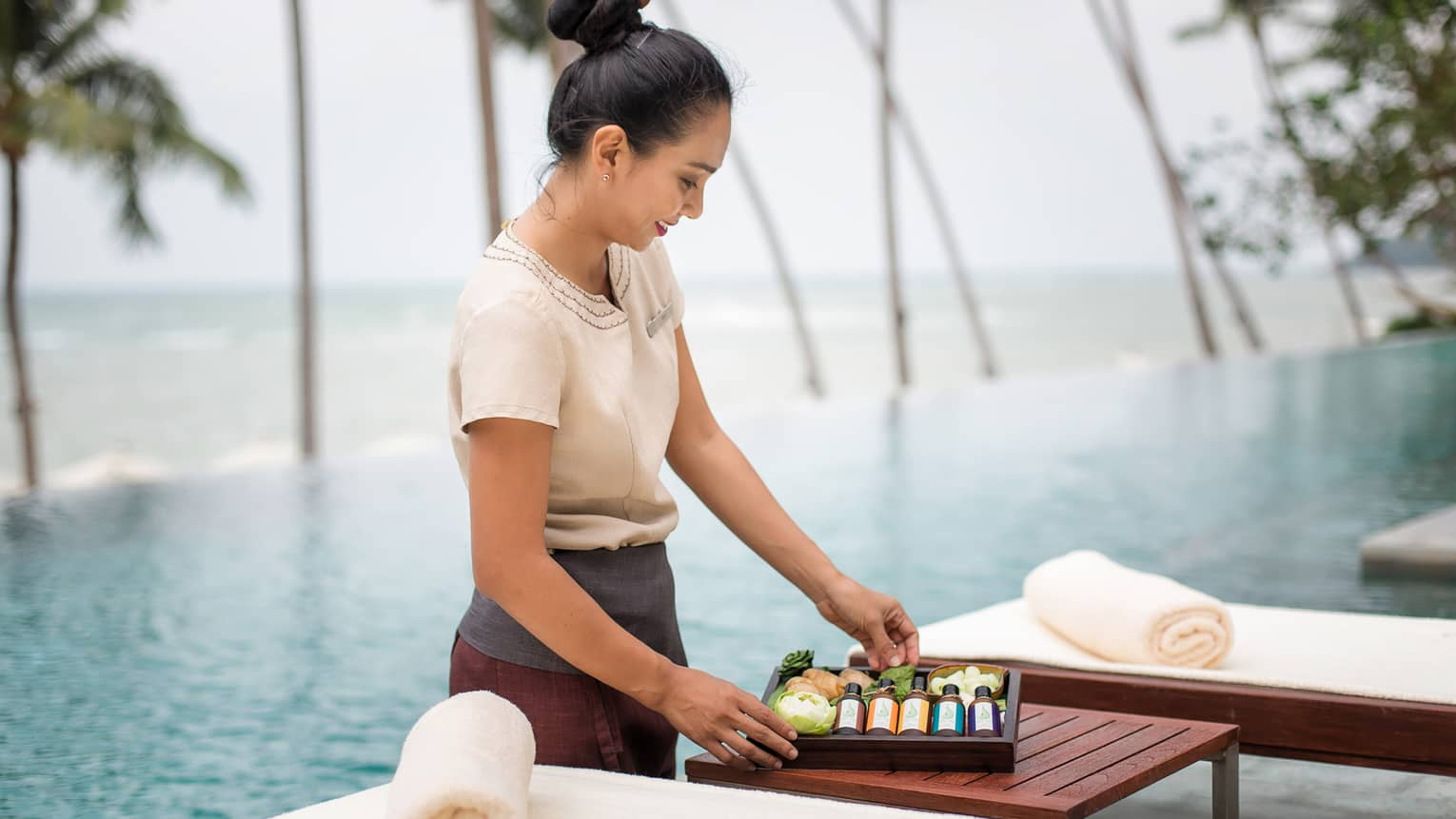 Spa attendant stands in front of swimming pool, holds wood box with bottles, soaps