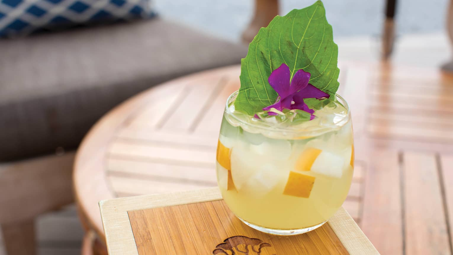 Waimea Burro yellow cocktail with cucumber, fruit pieces, large leaf, flower garnish