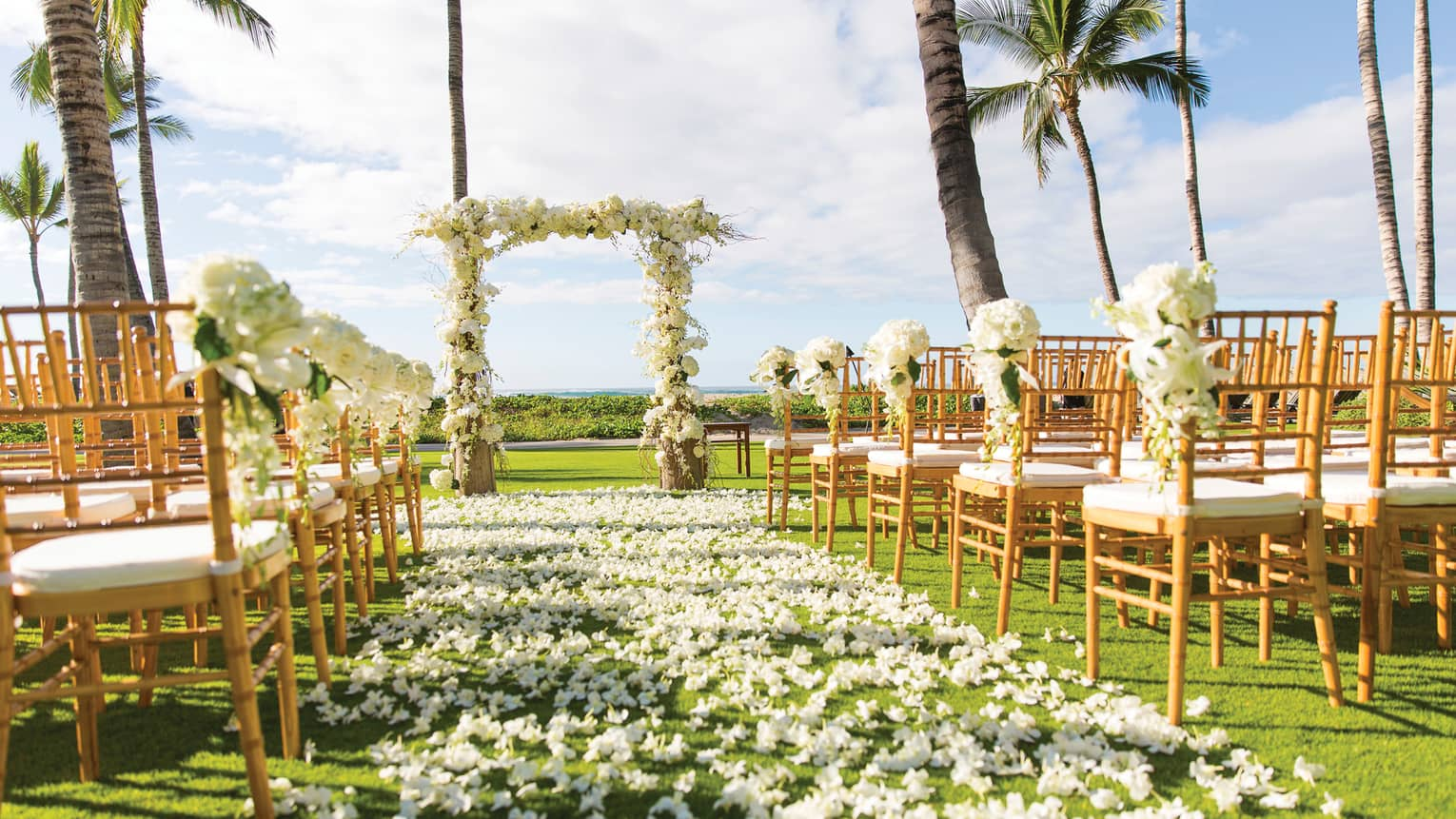 Outdoor wedding ceremony set up, white flowers along aisle between rows of chairs, altar
