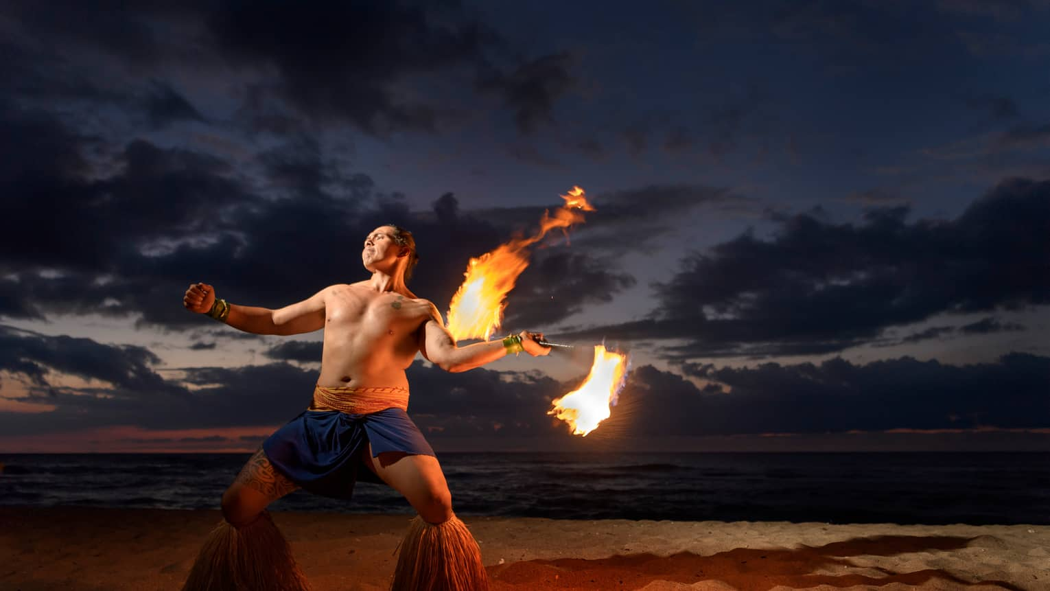 Man wearing traditional Polynesian outfit dances with torch on beach at night