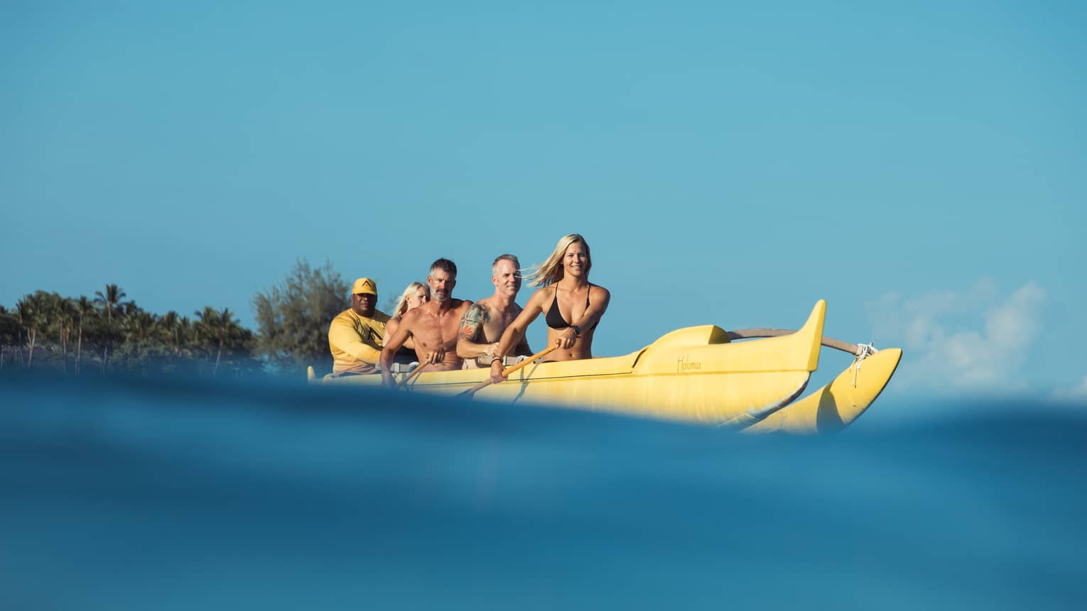 Group of friends with paddles row in large yellow canoe, Four Seasons resort staff at back