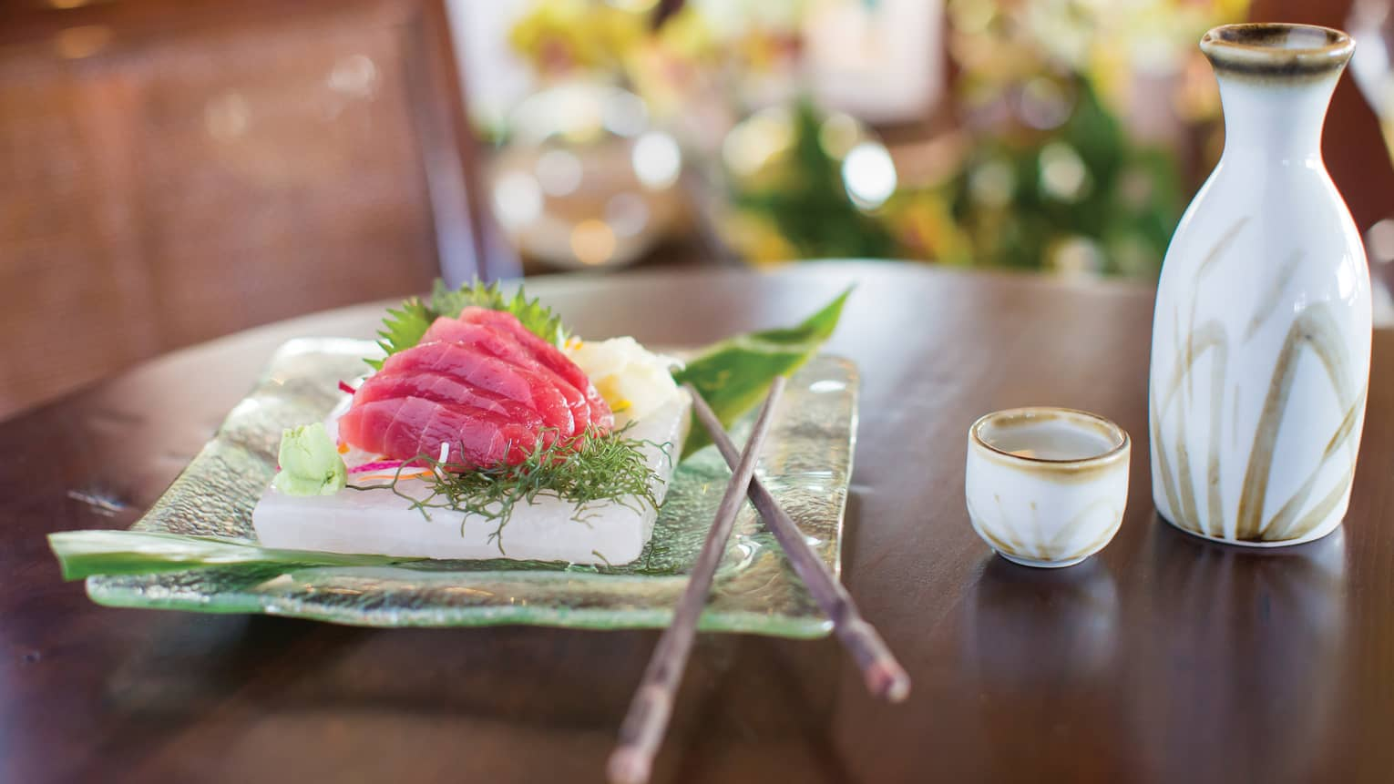 Slices of raw sashimi fish on glass plate next to sake cups