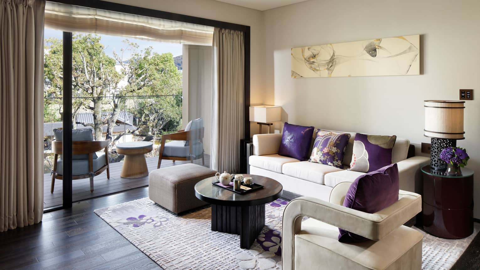 Living room sofa, armchair with plush purple pillows by open patio door, chairs