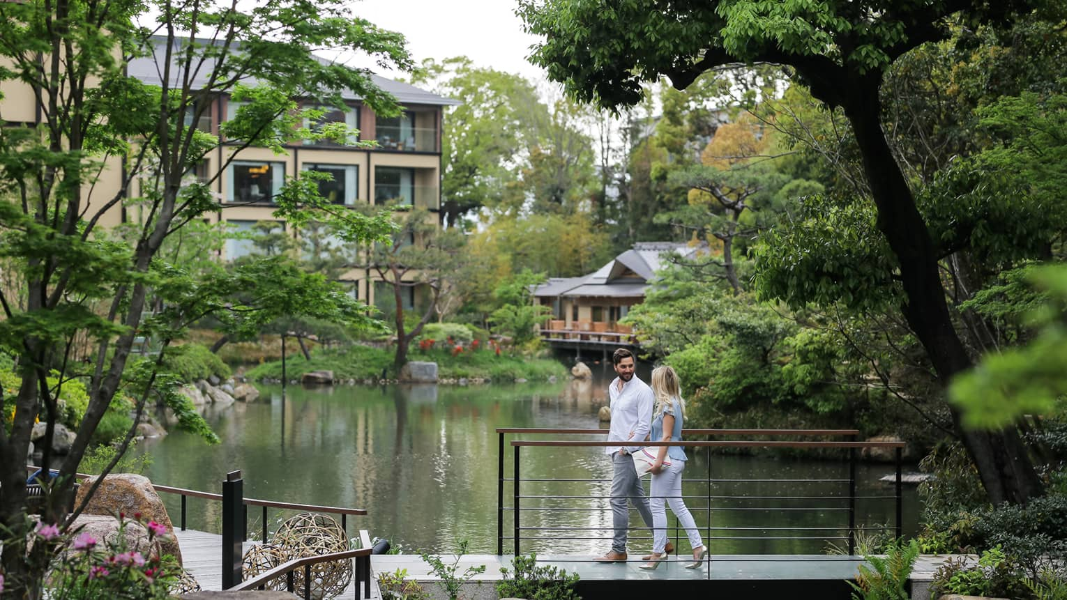 Couple walks across small bridge over pond surrounded by trees
