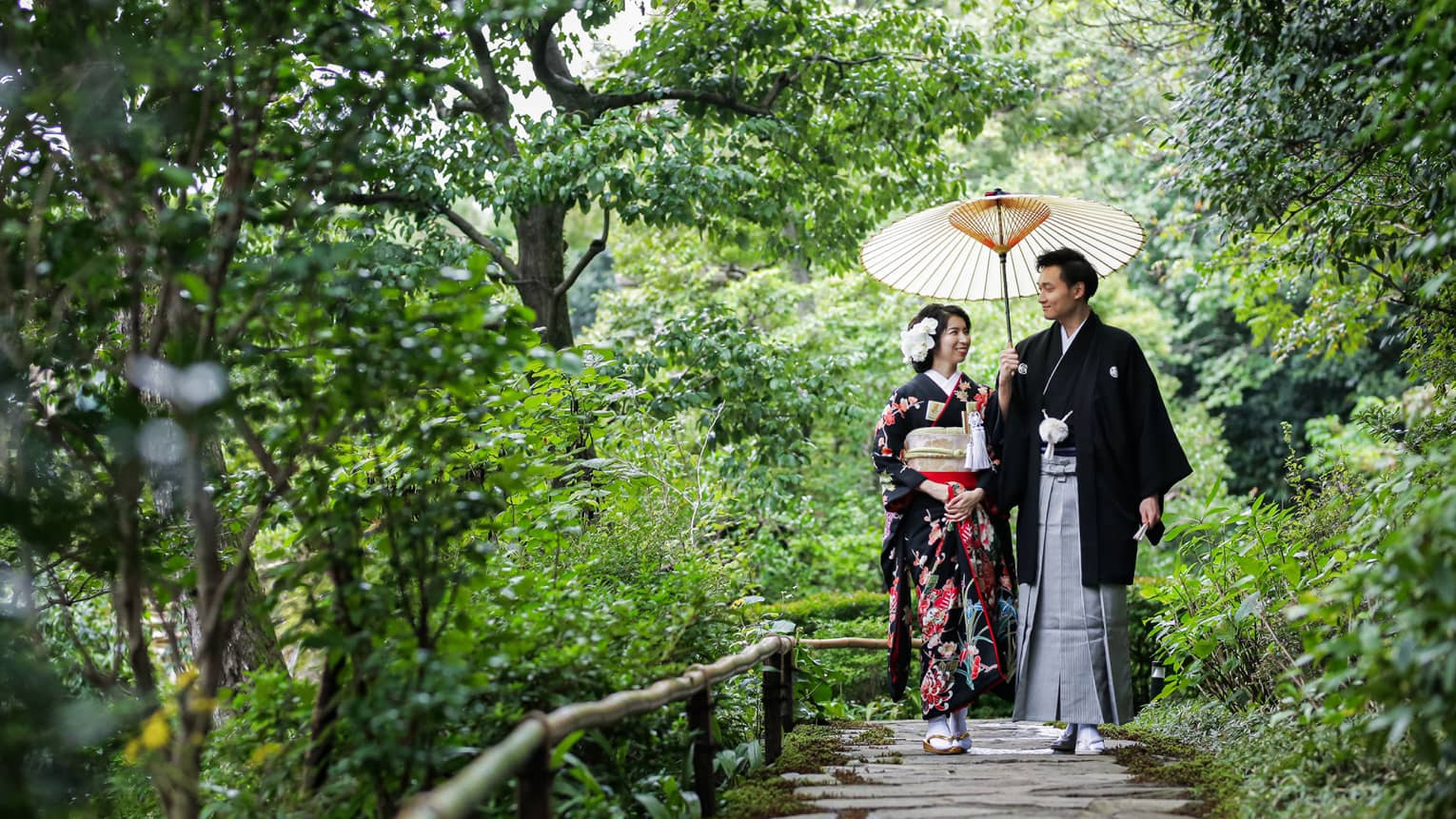 Couple wearing traditional Kyoto dress walk down stone path surrounded by trees