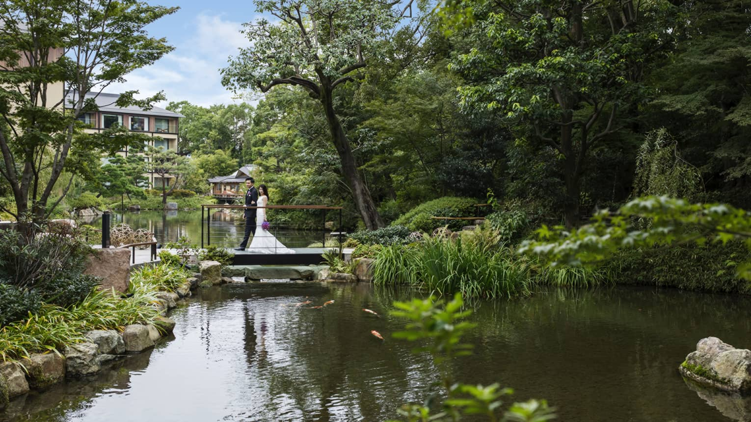 Bride and groom walk across small bridge over pond under trees
