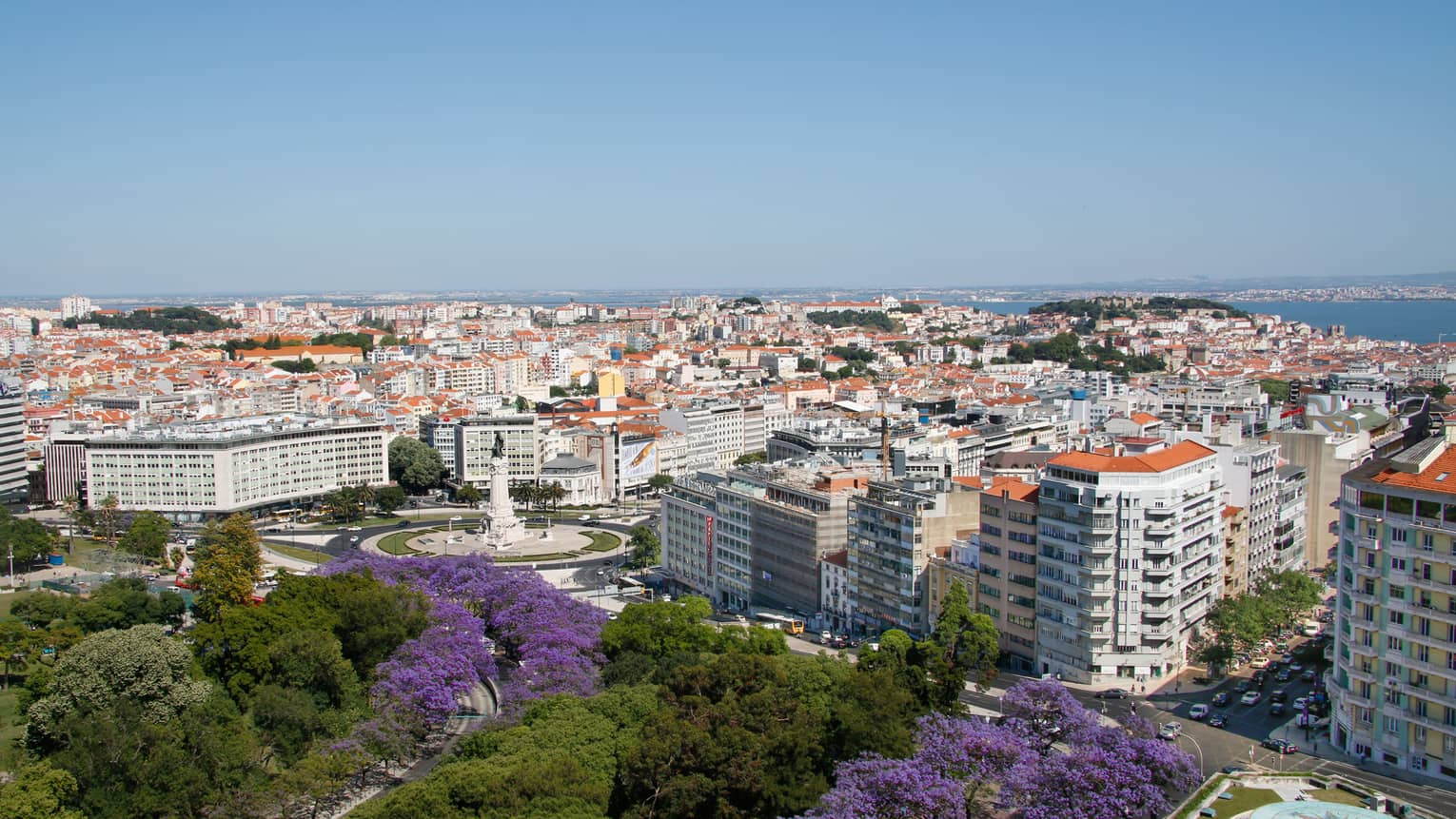 View over sunny Lisbon skyline with gardens, high rise buildings, rooftops