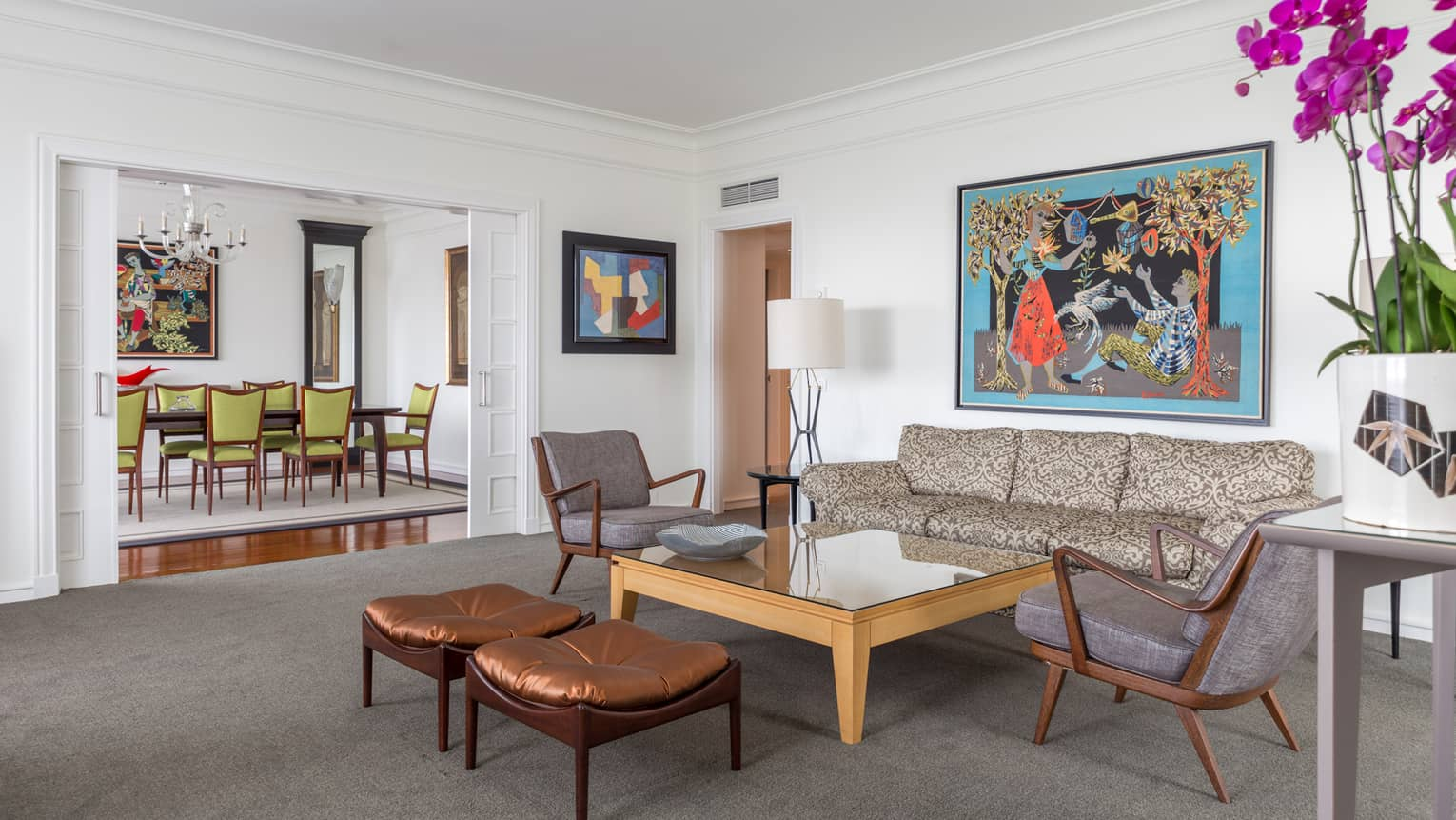 Residency Suite with mid-century modern living room vignette, colorful painting and dining room view