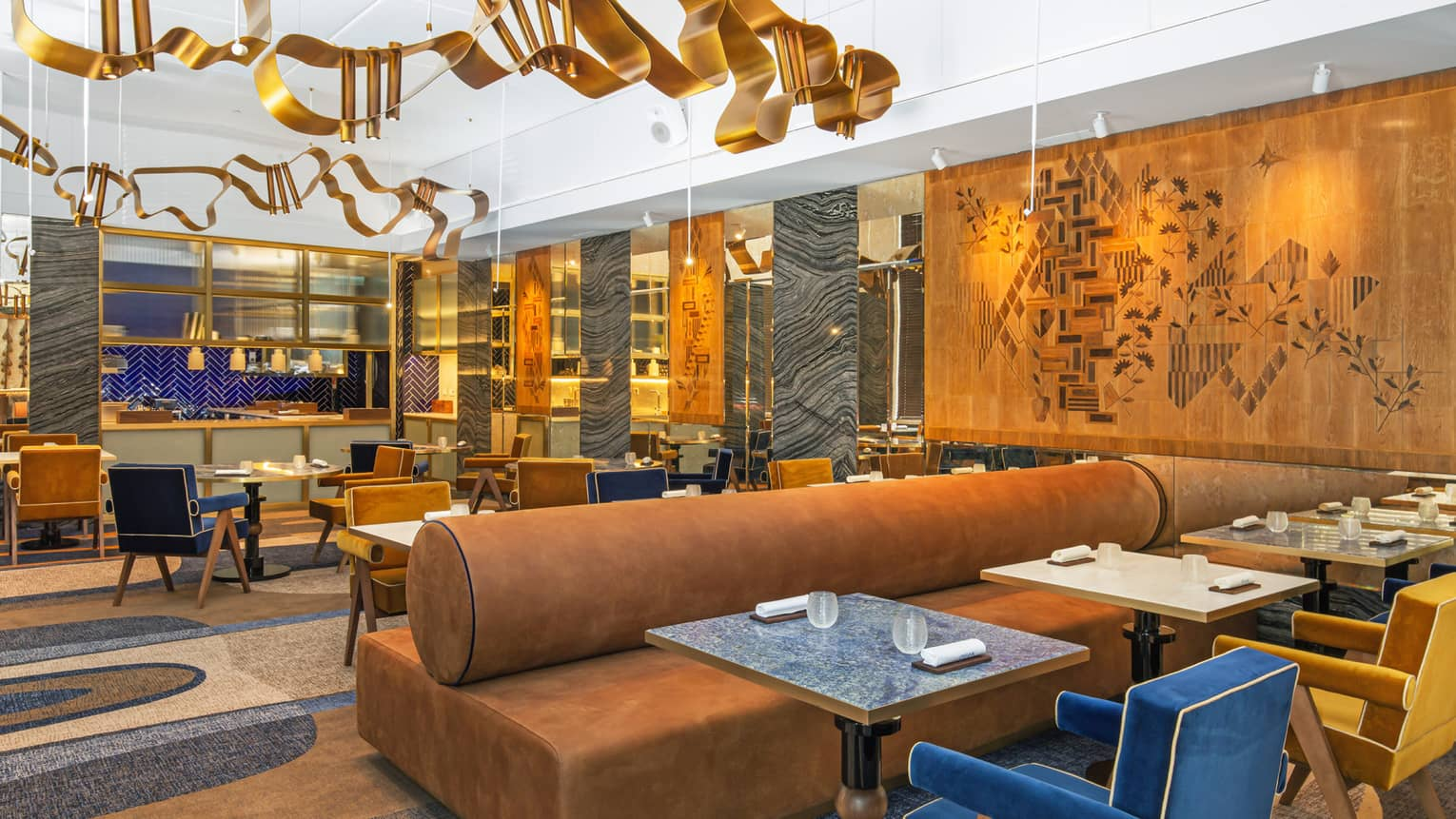 Modern dining area with gold, blue and deep camel accents and art flanking walls and ceiling
