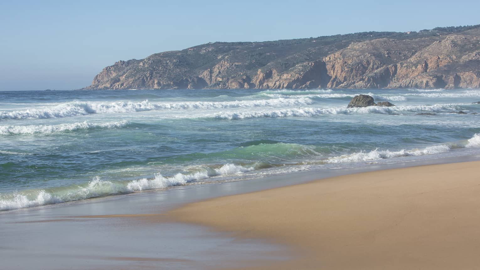 Blue waves roll onto shore on serene Guincho Beach in Portugal