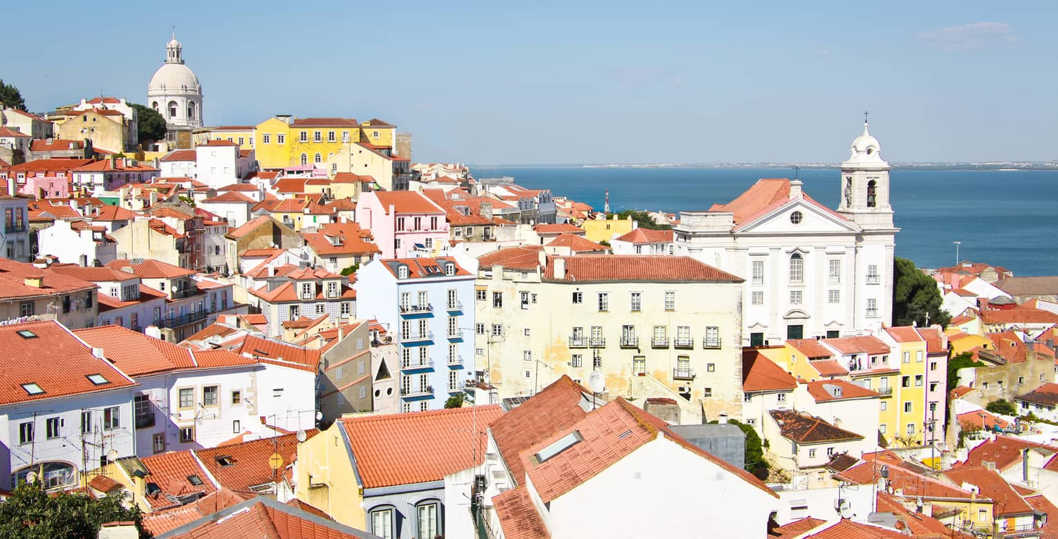 Aerial view of Lisbon skyline and rooftops on sunny day white houses, apartment buildings with brown roofs, white church
